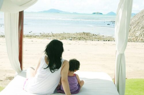 mom with a child watching the beach on the bed