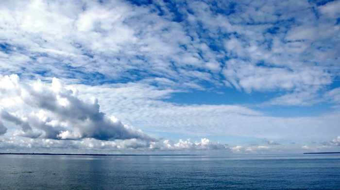 The sea on a background of the blue sky and clouds