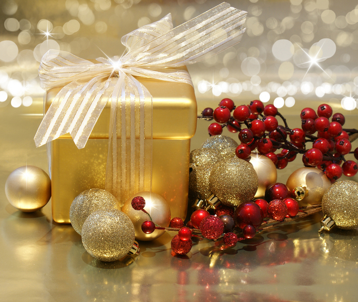 Christmas background with gift box, berries and baubles on gold background