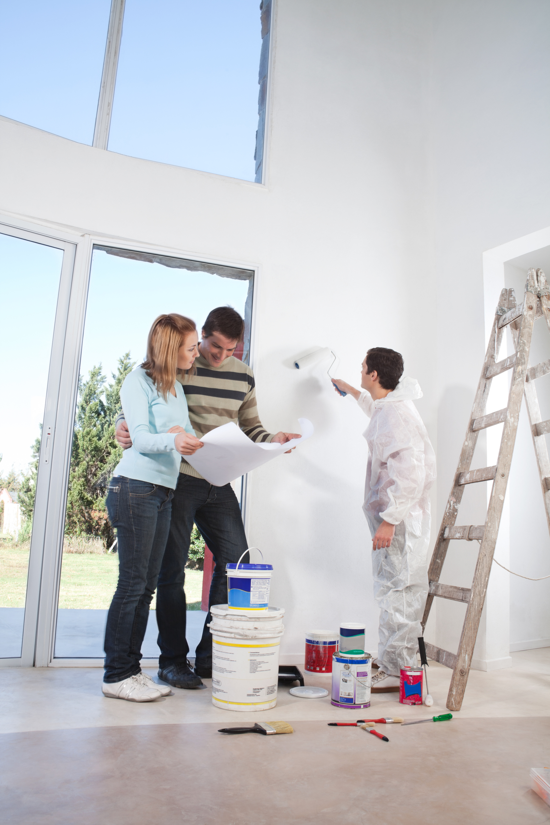 Young couple looking at blueprint while worker painting their house